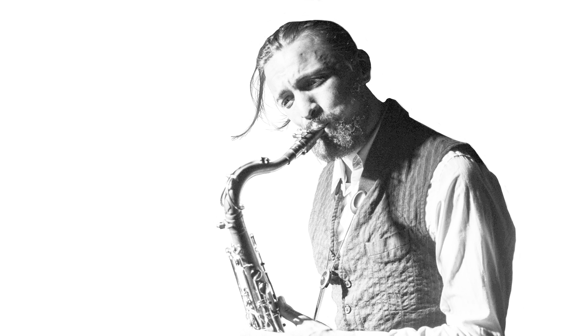 black and white photo of Aurélien Tomasi blowing in his tenor saxophone. Photo credited to Peter Graham. Design by musicos Productions